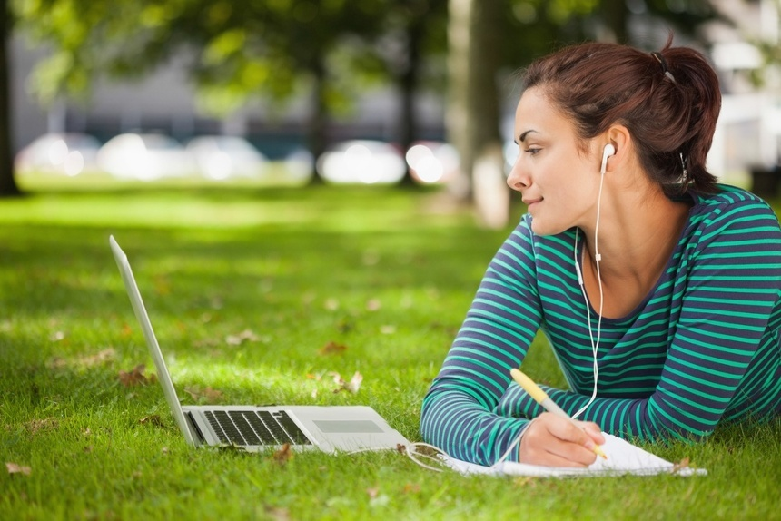 Attractive casual student lying on grass taking notes on campus at college