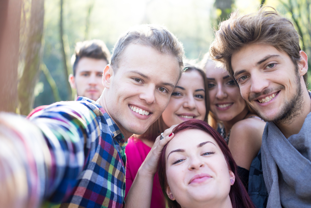 Young people having good time together in park on river and taking selfie