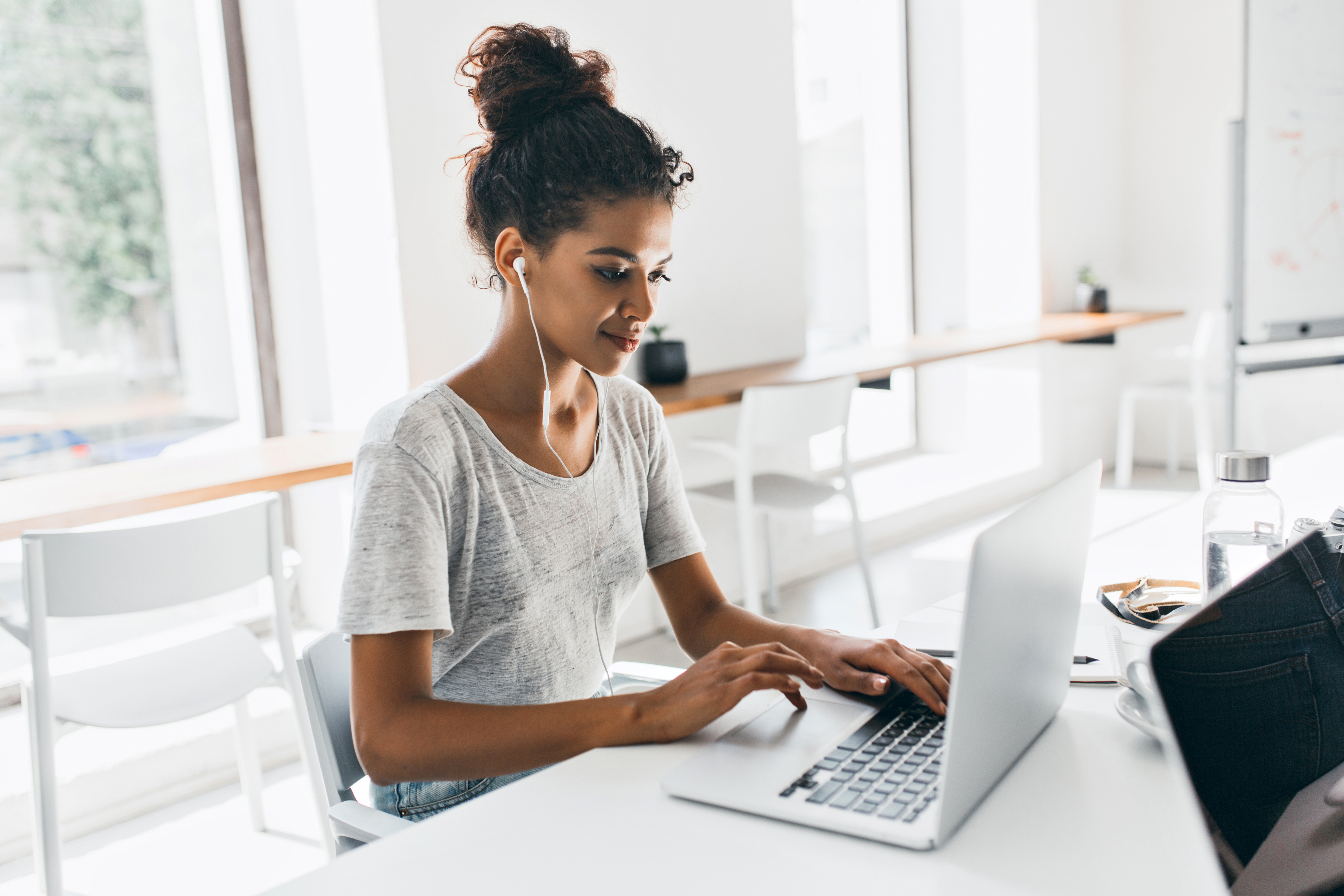 romantic-african-woman-with-trendy-hairstyle-sitting-at-her-workplace-and-analysing-data-indoor-portrait-of-black-female-student-working-with-laptop-before-exam